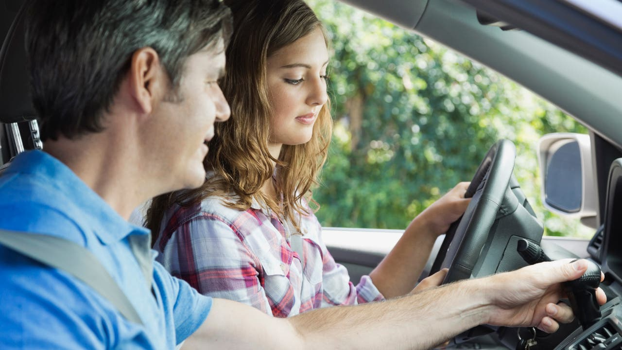 girl and dad driving car