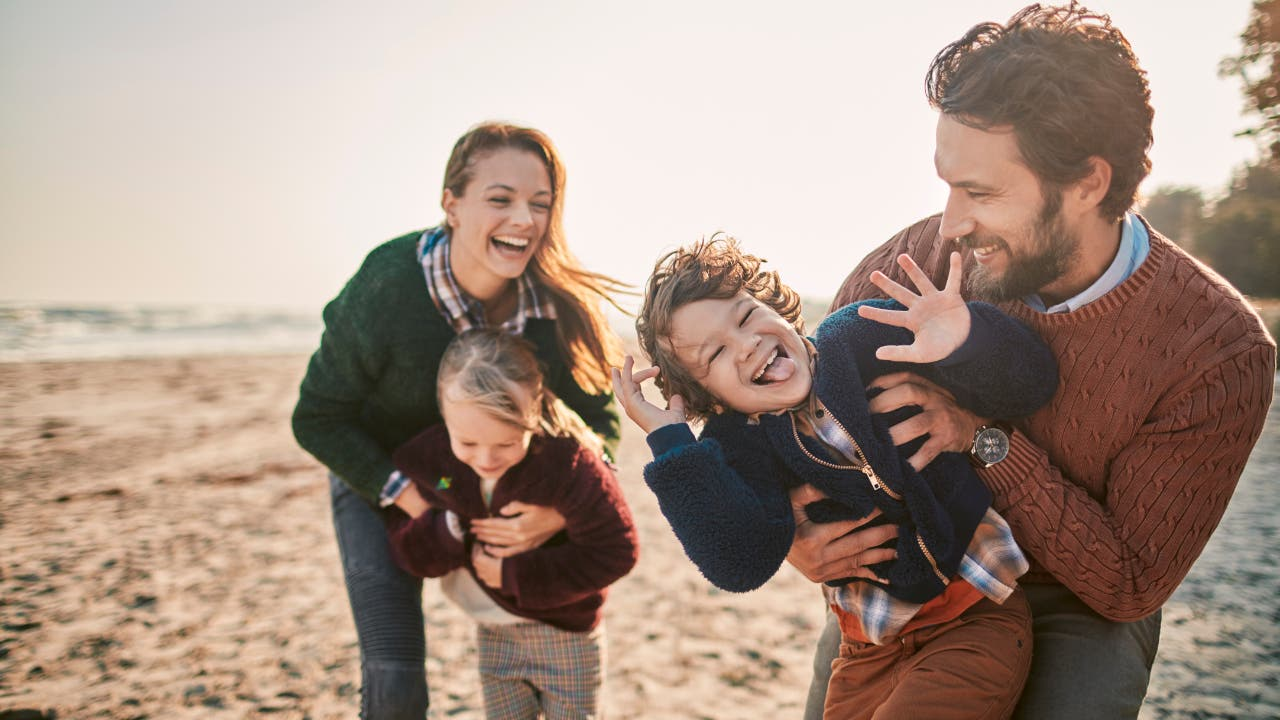young family laughing at the beach