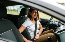 woman in car putting on seat belt