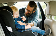 man buckling his son into his car seat