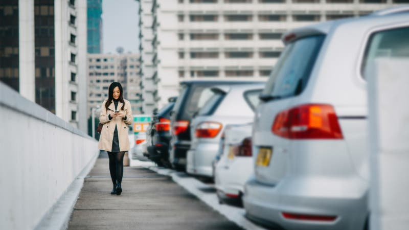woman texting next to a row of cars