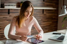 Woman at desk looking at tablet with credit card