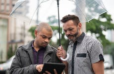 Two people under umbrella using tablet