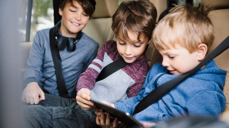 three boys looking at a tablet in the back seat of a car