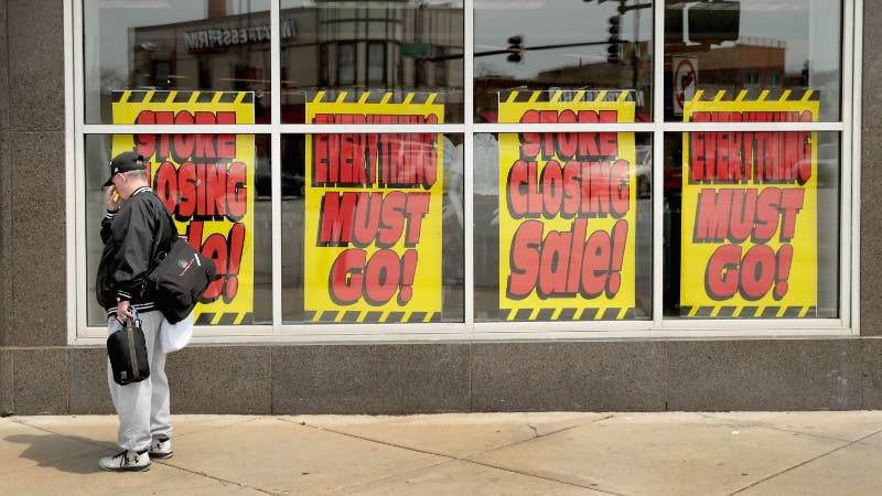 Signs in the window of a Sears store advertise its closing.