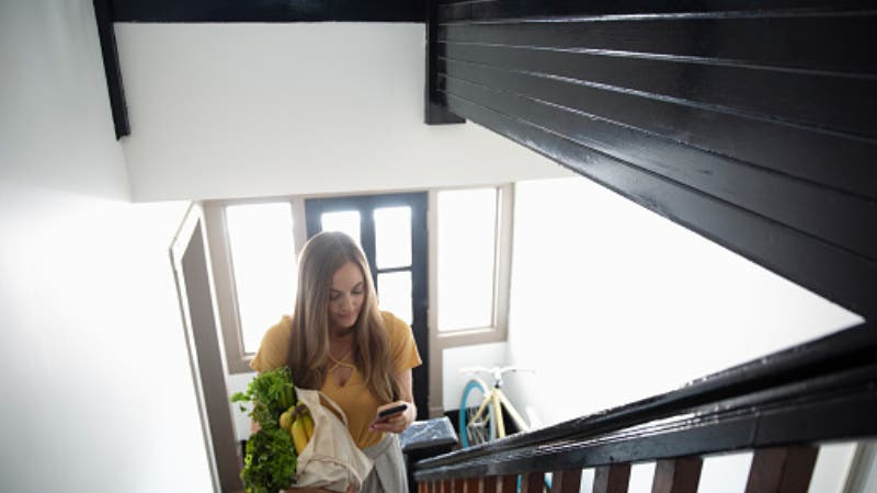 woman taking groceries up the stairs