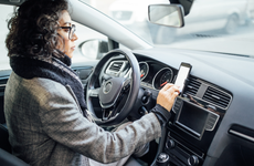 woman in car looking at cellphone