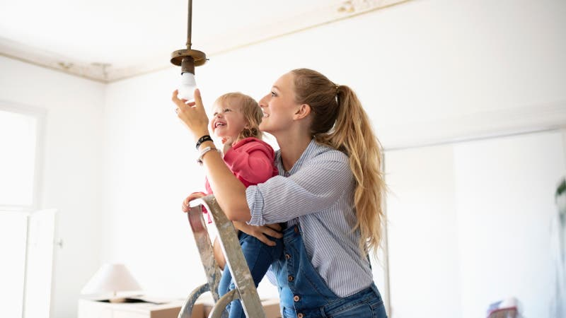 Mom changing light bulb with baby