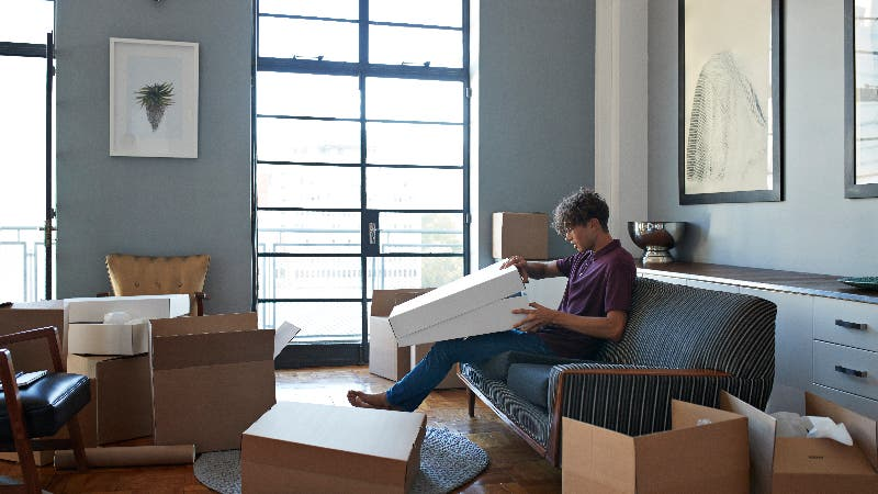 A man unpacking boxes in an apartment