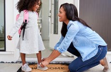 Woman ties daughter's shoes