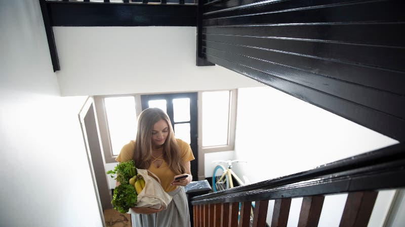 Woman walks up apartment stairs with groceries