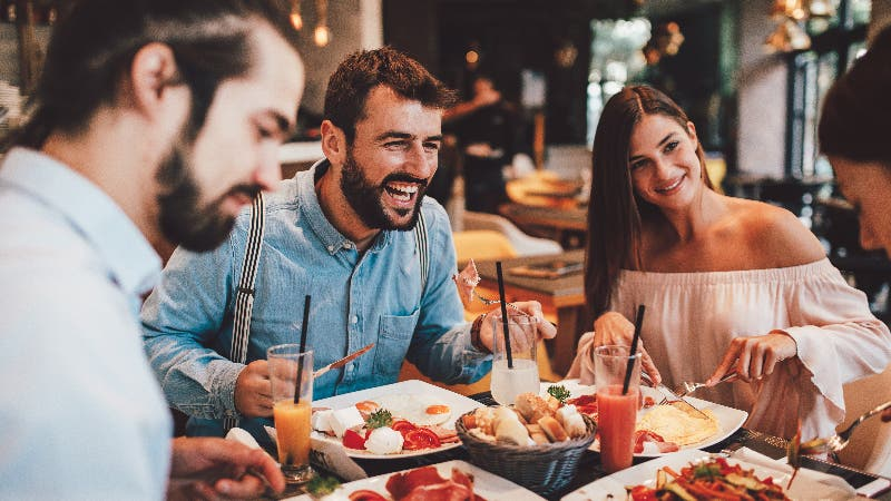 group of four friends eating a meal out at a restaurant