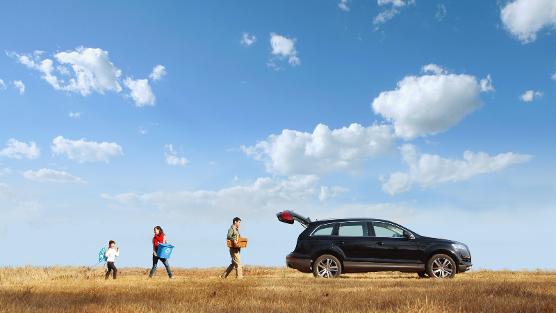 family in a field with their car