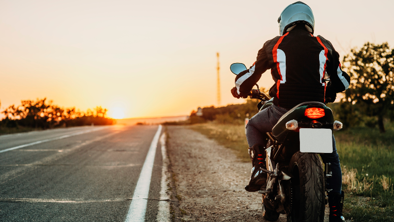 man on motorbike riding on roadside