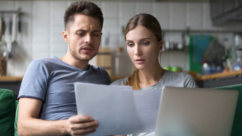 A couple looks at paperwork and seems confused.