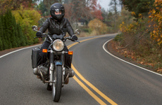 women riding motorcycle on country road