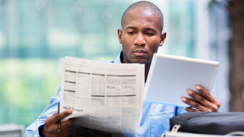A man studies the Wall Street Journal and considers placing a trade