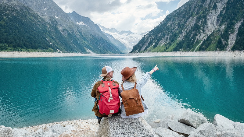 two people with backpacks sit on rock near lake and mountains
