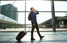 man walking through airport with suitcase while talking on cell phone