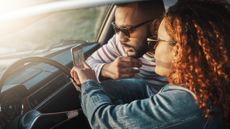 couple looking at mobile phone in car