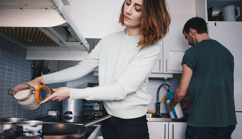 Young roommates preparing food in apartment