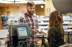 Young man pays for groceries with credit card