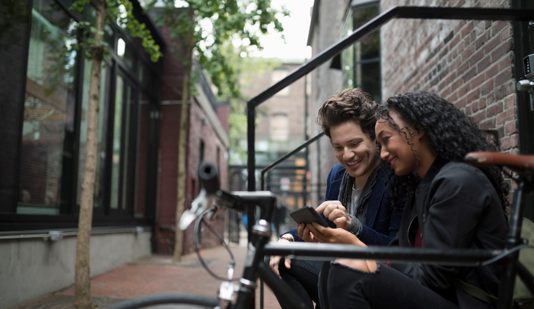 Young couple texting with smart phone on urban stoop