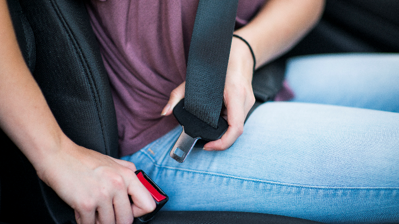 Young female buckling up in car