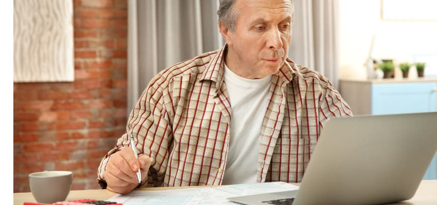 man filling out taxes at home