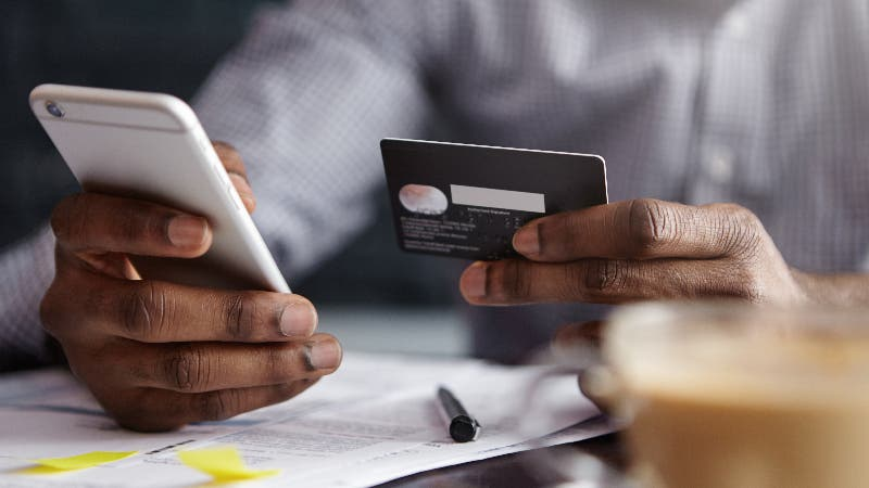 man holding credit card in one hand and phone in the other