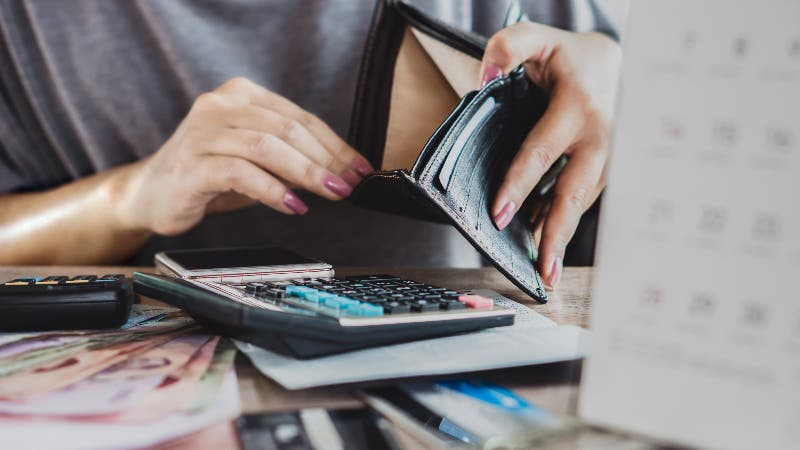 woman at desk with open wallet, calculator and papers