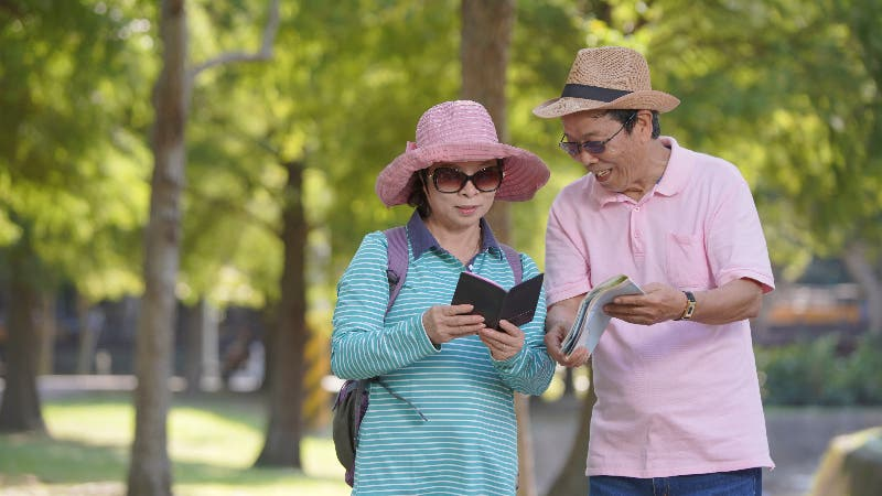 An older Asian couple are looking at travel books
