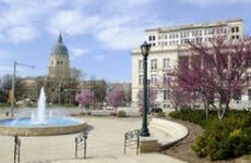 Shot of Topeka, Kansas with buildings in the distance and an ornate fountain in the middle.