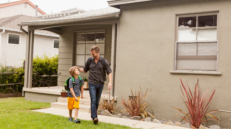 Father walking son to school in front of house