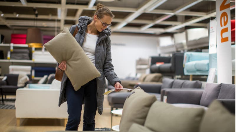 Woman looks at price tag of couch in furniture store