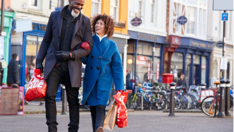 Middle-aged couple strolling arm-in-arm with shopping bags