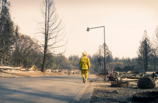 Fire fighter walking along a street where every home burned to the ground