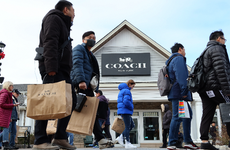 Consumers walking past a Coach store with shopping bags.