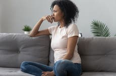 Woman sits on the couch looking bothered.