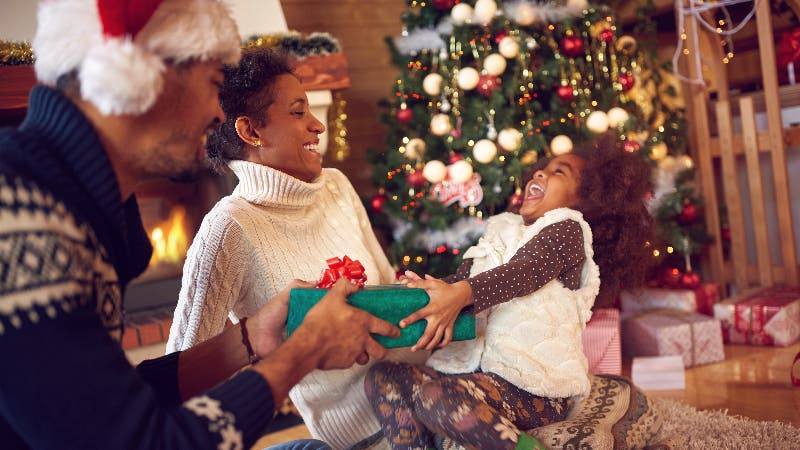 family around the christmas tree while parents hand gift to daughter
