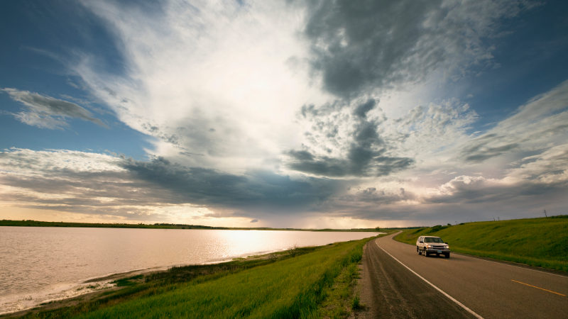 SUV driving along a lake in McHenry County, North Dakota