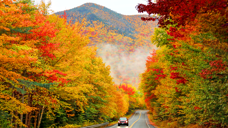 SUV driving down the Kancamagus Highway in Northern New Hampshire