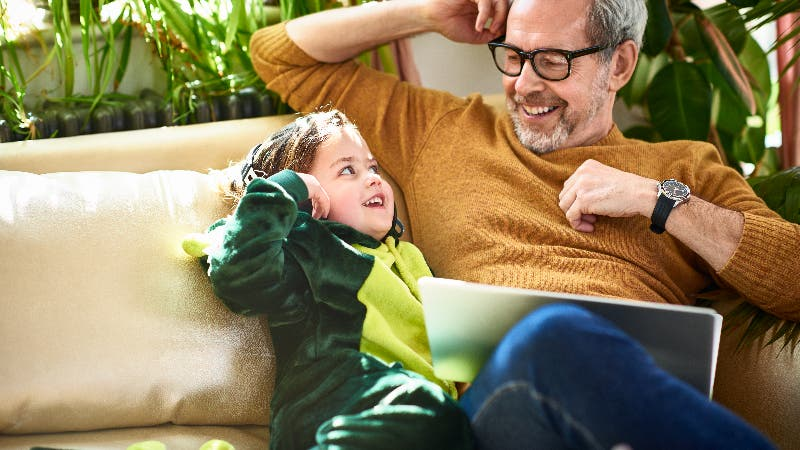 A middle age man plays with his granddaughter on the couch