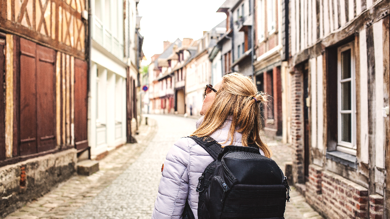 woman with backpack traveling solo in village abroad