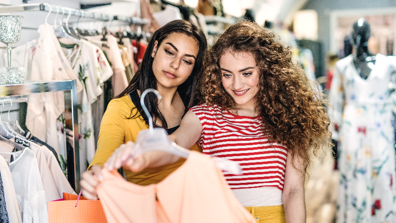 two women looking at shirt on hanger in store