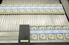 Stacks of dollars bills moving through a machine at the U.S. Bureau of Engraving and Printing
