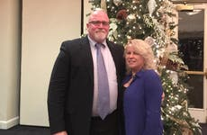 Christopher Lond and his wife stand by a Christmas tree