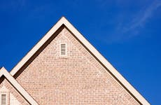 The peaks of a house in front of a blue sky