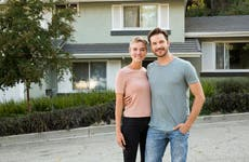A young couple of homebuyers stands in front of a house