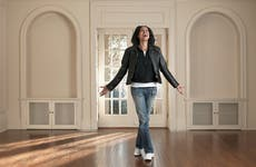 A woman celebrates her new home in an empty room